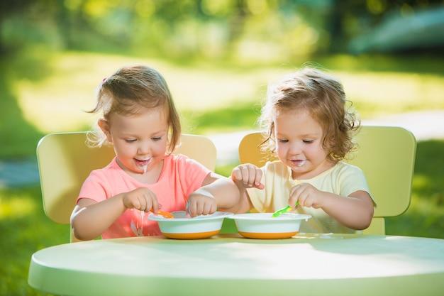Twee kleine meisjes zitten aan een tafel en samen eten tegen groen gazon