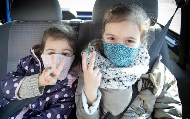 Twee kleine meisjes zitten in een auto op de achterbank en dragen maskers tijdens de pandemie