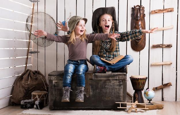 Twee kleine meisjes zitten op houten borst met handen omhoog