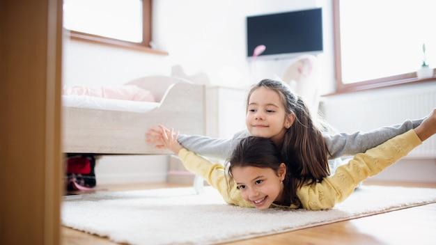 Twee kleine meisjes zusjes binnenshuis, spelen op de vloer in de slaapkamer.