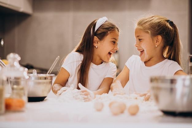 Twee kleine meisjes zusjes koken in de keuken