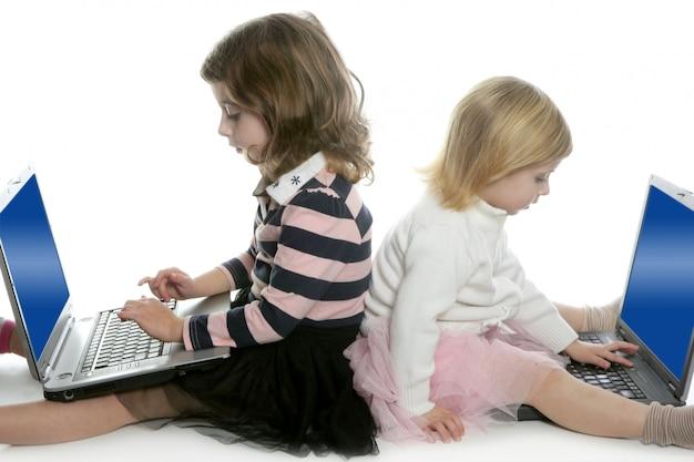 Twee kleine meisjeszus met computerlaptops