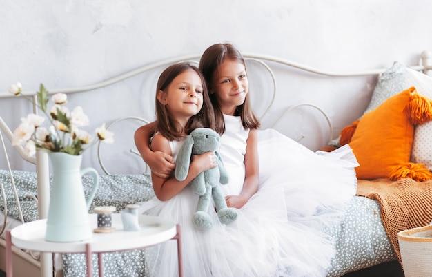 Twee kleine meisjeszusjes zitten op een bed in de slaapkamer in prachtige jurken. tedere jeugdvriendschap
