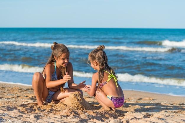 Twee kleine meisjeszusters bouwen zandkasteel