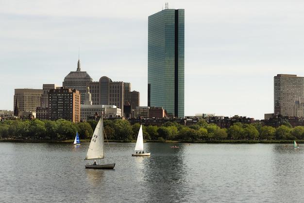 Twee kleine metalen boten zeilen in de buurt van een stad op een zonnige dag