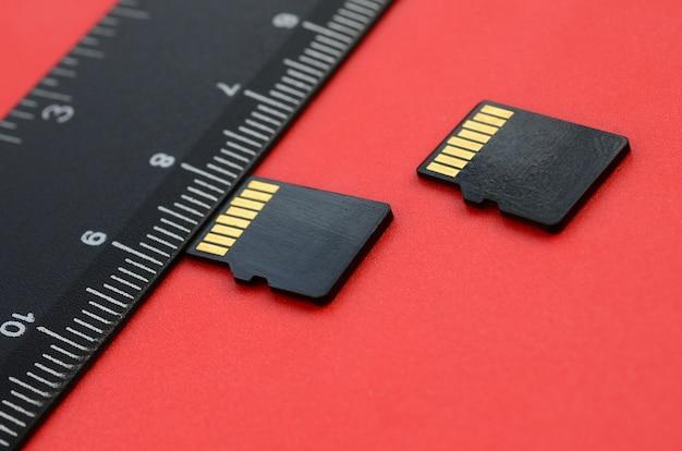 Twee kleine micro sd-geheugenkaarten liggen op een rode achtergrond