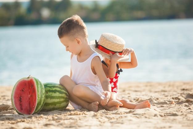 Twee kleine mooie kinderen op het strand met watermeloenen. schattige kinderen spelen in de buurt van de kust lachend. vrolijke kinderen.