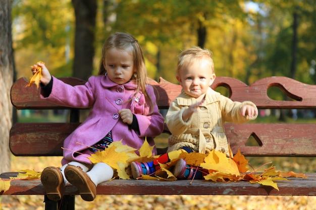 Twee kleine mooie meisjes die op de bank in warme de herfstdag zitten