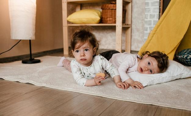 Twee kleine mooie tweelingmeisjes spelen liggend op de vloer met koekjes in hun handen dichtbij de gele tipi.