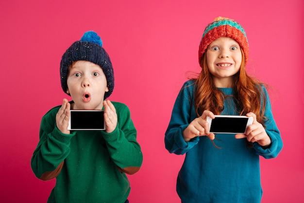Twee kleine opgewonden kinderen tonen displays van mobiele telefoons.