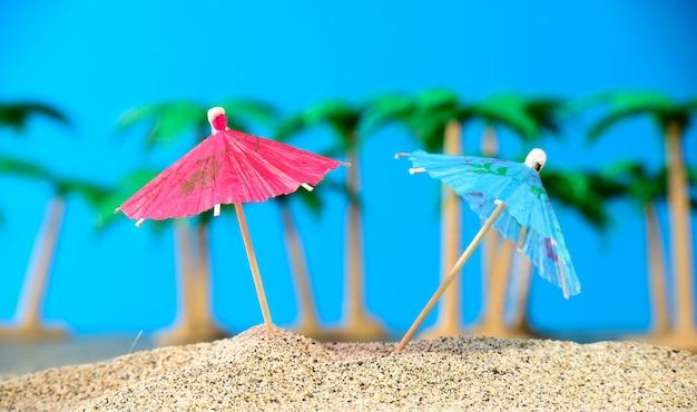 Twee kleine parasols op een strand