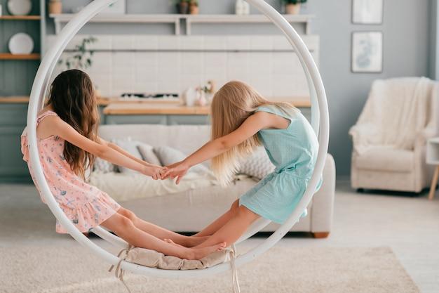 Twee kleine rare meisjes met lang haar die hun gezichten bedekken die in schommeling in kinderkamerbinnenland zitten. grappige kinderen voor de gek houden met elkaar