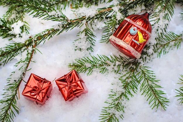 Twee kleine rode glanzende dozen met kerstcadeaus en kerstspeelgoed