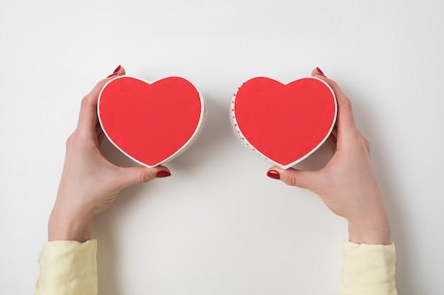 Twee kleine rode hartvormige dozen op vrouwelijke handen op. cadeau voor valentijnsdag