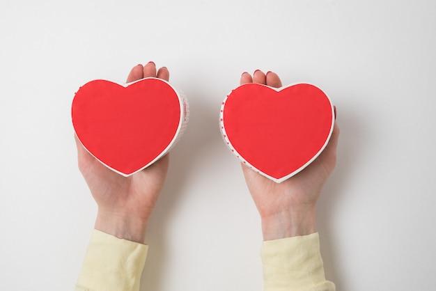 Twee kleine rode hartvormige dozen op vrouwelijke palmen op witte achtergrond. cadeau voor valentijnsdag