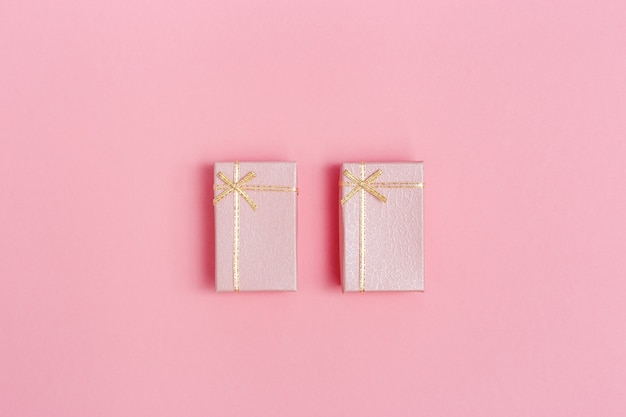Twee kleine roze geschenkdozen op roze papieren ondergrond