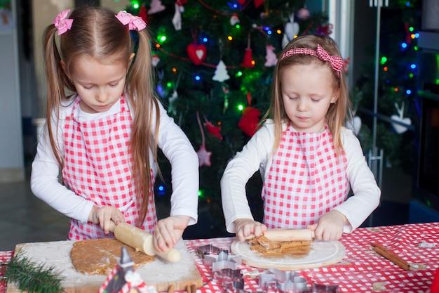 Twee kleine schattige meisjes maken peperkoekkoekjes voor kerstmis
