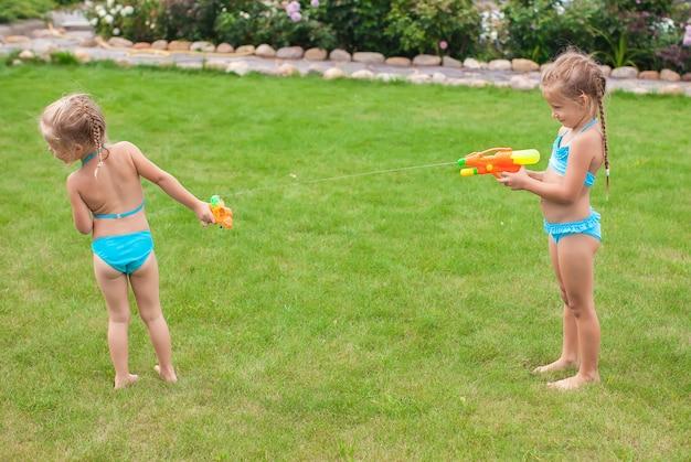 Twee kleine schattige meisjes spelen met waterpistolen in de tuin