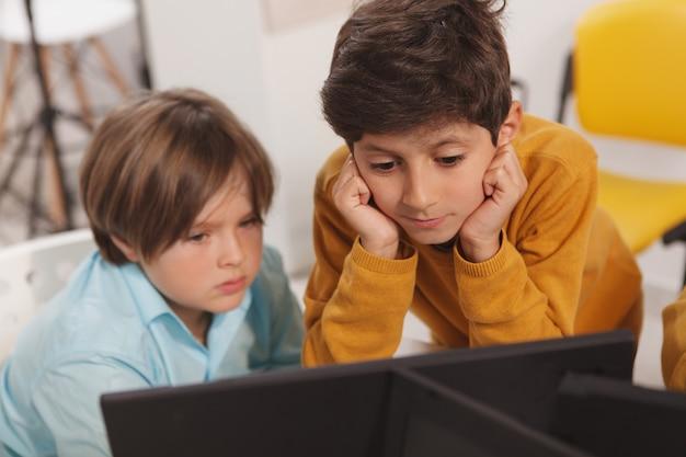 Twee kleine schooljongens die op school aan een computer samenwerken