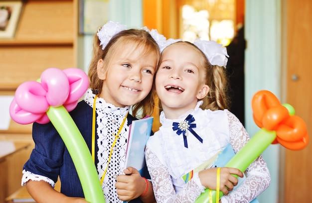 Twee kleine schoolmeisjes zijn blij elkaar te zien