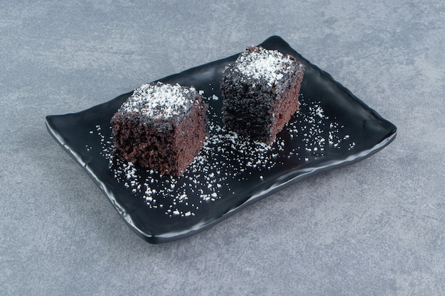 Twee kleine stukjes brownie op een donker bord