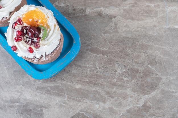 Twee kleine takes op een blauwe schotel op een marmeren oppervlak