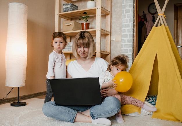 Twee kleine tweelingmeisjes verhinderen dat hun moeder thuis op de computer werkt.