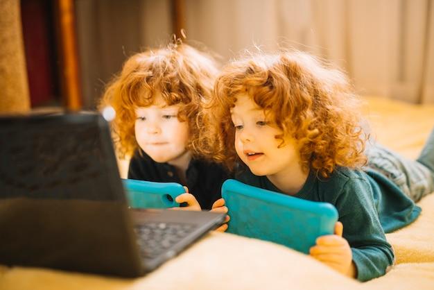 Twee kleine tweelingzusters die digitale tablet houden liggend op bed die laptop bekijken