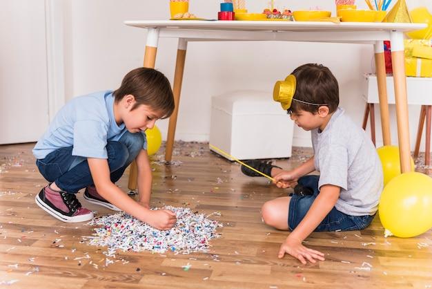 Twee kleine vrienden verzamelen confetti op verdieping in partij