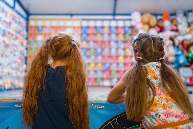 Twee kleine vriendinnen spelen in de schietgalerij voor kinderen, speeltuin in het uitgaanscentrum. speelruimte binnen, speelkamer