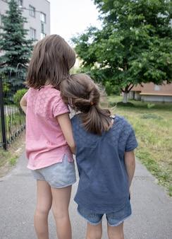 Twee kleine vriendinnen zusjes knuffelen op een wandeling in de zomer.