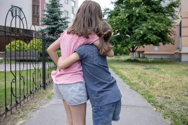 Twee kleine vriendinnen, zussen knuffelen elkaar tijdens een wandeling in de zomer