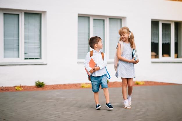 Twee kleine vriendjes gaan naar school. schoolkinderen. terug naar school