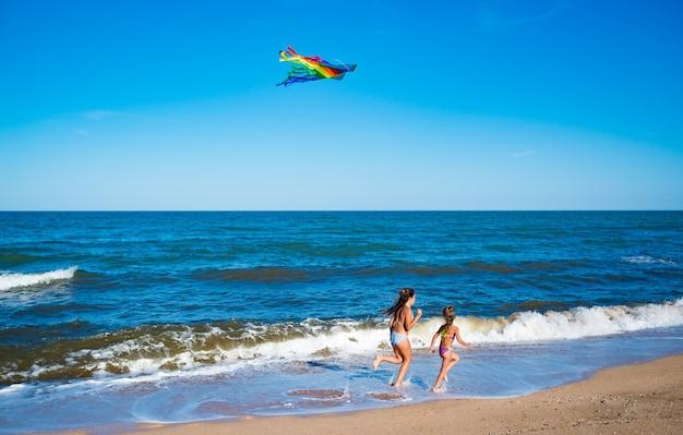 Twee kleine vrolijke vrolijke meisjes rennen met een vlieger op de zanderige kust bij de zee.