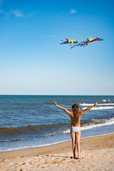 Twee kleine vrolijke vrolijke meisjes rennen met een vlieger op de zanderige kust bij de zee