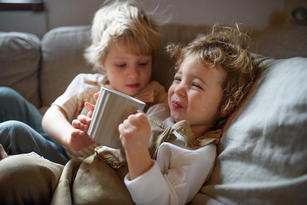 Twee kleine zieke kinderen, broer en zus die thuis in bed liggen en thee drinken.