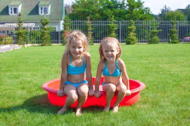Twee kleine zusjes dartelen en spetteren in hun tuin