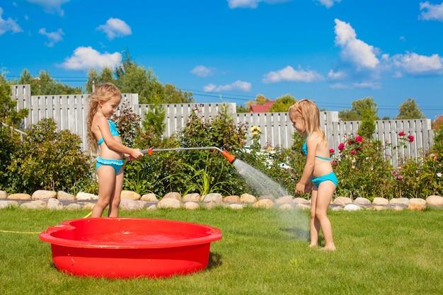 Twee kleine zusjes dartelen, spetteren en hebben plezier in hun tuin