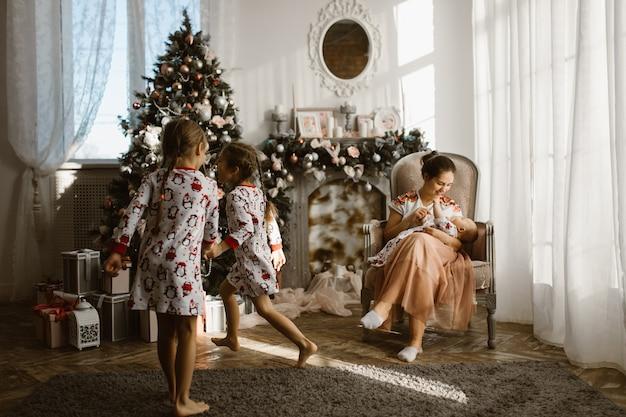 Twee kleine zusjes in pyjama die plezier hebben nieuwjaarsboom met cadeaus in de lichte, gezellige kamer en hun moeder zit in de fauteuil met kleine baby naast de open haard. .