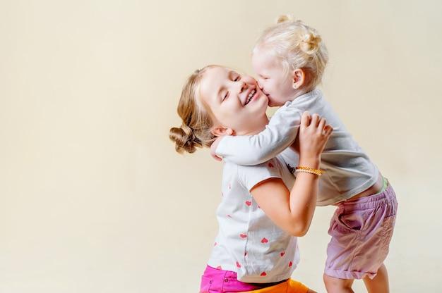 Twee kleine zusjes knuffelen en kussen elkaar op een lichte achtergrond. het concept van een gelukkig gezin, ouderschap, zusterliefde