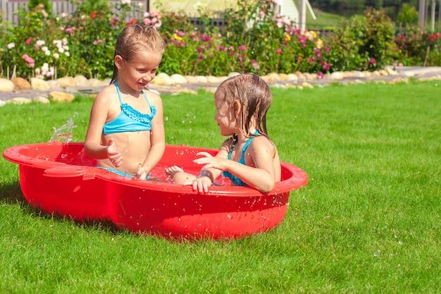 Twee kleine zusjes spelen en spatten in het zwembad op een warme zonnige dag