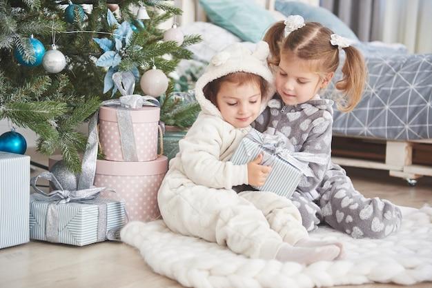 Twee kleine zustermeisjes openen hun cadeaus bij de kerstboom in de ochtend op het dek