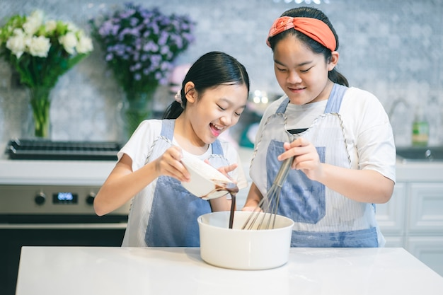 Twee kleine zusters die het cakedeeg voorbereiden.
