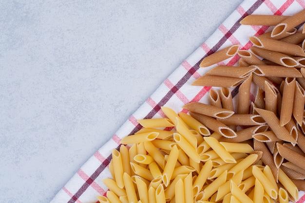 Twee kleuren rauwe pasta op gestreept tafelkleed