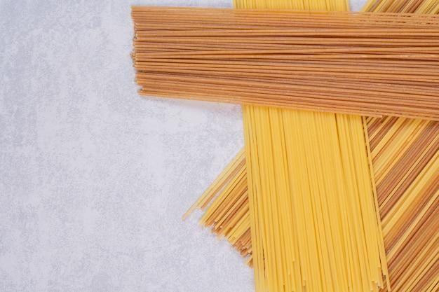 Twee kleuren van ruwe spaghettideegwaren op witte oppervlakte
