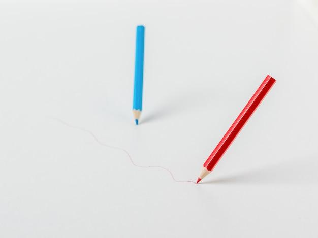 Twee kleurpotloden die op een witte achtergrond trekken. schrijfwaren en schoolbenodigdheden.