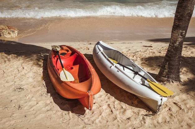 Twee kleurrijke kajaks op zandstrand.