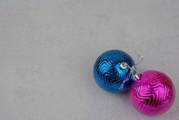 Twee kleurrijke kerstballen op grijze muur.