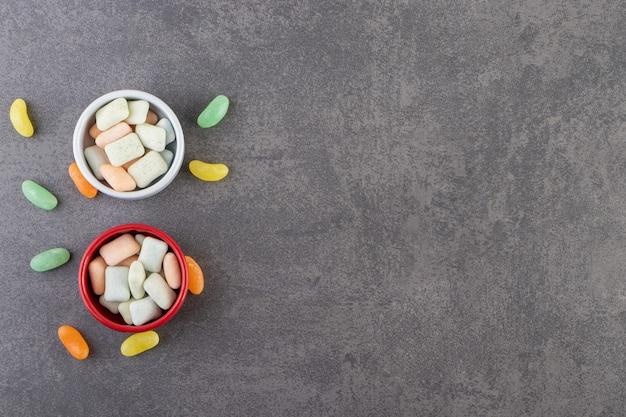 Twee kleurrijke kommen kauwgom op stenen tafel.