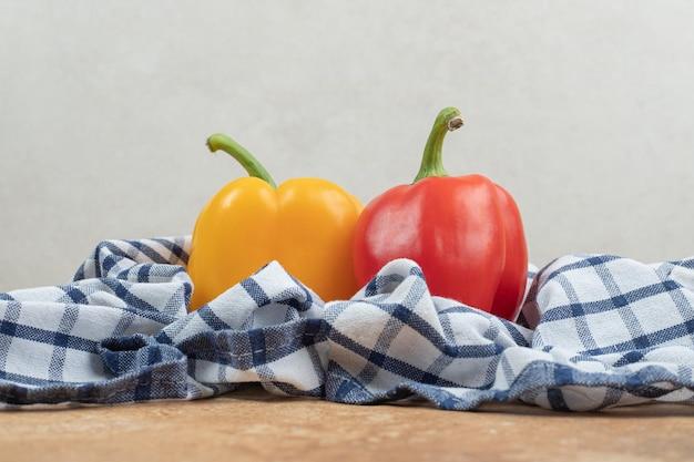Twee kleurrijke paprika's die op tafellaken liggen